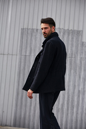 Fashion beard style business handsome male model posing in style clothing blue jacket and trousers on street wall outdoors background. Closeup toned portrait.