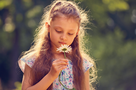 Photo for Beautiful kid girl looking on chamomile flower on nature summer green background. Closeup bright portrait - Royalty Free Image