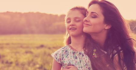 Photo pour Happy enjoying mother hugging her relaxing joying kid girl and breathing fresh air on sunset bright summer background. Closeup toned color portrait - image libre de droit