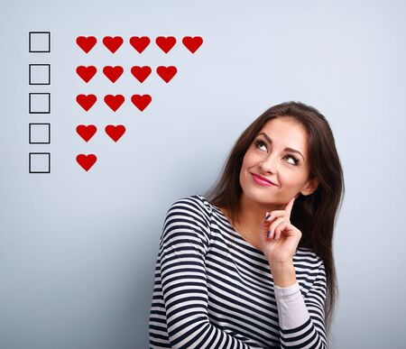 Photo for Thinking smiling young woman looking up and voting on five red hearts ranking on blue background with empty copy space. Closeup - Royalty Free Image