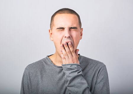 Photo for Tired wanting to sleep young man yawning and closed mouth the hand on blue background. Closeup - Royalty Free Image