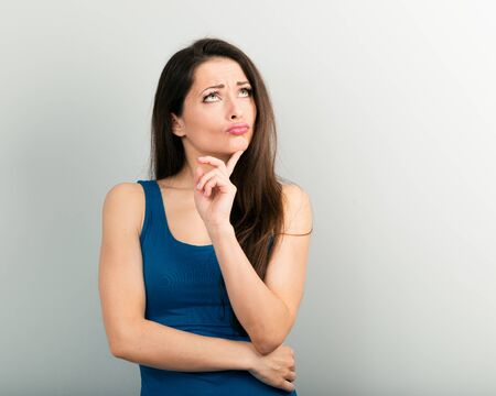 Photo for Beautiful young angry unhappy woman with finger sign have an idea and looking up in casual blue shirt and long hair. Closeup portrait - Royalty Free Image