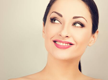 Photo pour Beautiful woman with healthy clean face skin looking up and thinking with toothy smile. Correction eyebrows shape. Dental perfect health. Studio blue background. Closeup toned color portrait - image libre de droit