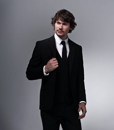 Photo pour Business sexy man in black fashion suit posing on gray bacground with serious face and folded arms. Closeup studio portrait - image libre de droit
