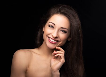 Photo pour Beautiful happy toothy laughing woman with brown hair looking happy on black background with empty copy space. Closeup beauty portrait - image libre de droit