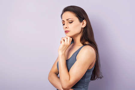 Photo pour Angry grimacing brunette woman thinking and looking down in gray t-shirt with folded arms on purple background with empty copy space. Closeup portrait - image libre de droit