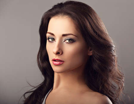 Photo pour Beautiful mysterious woman makeup face and healthy volume brown hair with wisdom emotional look on brown color background with empty copy space. Closeup portrait. - image libre de droit