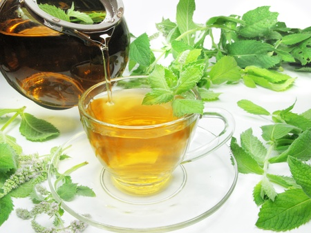 pouring mint tea into cup among leaves