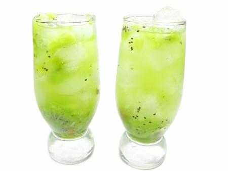 two glasses of fruit green drinks with ice and kiwi