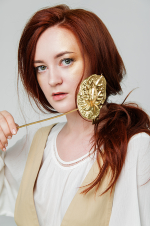 Foto per young beautiful woman has red hair creative gold make up are posing in a studio with flowers - Immagine Royalty Free