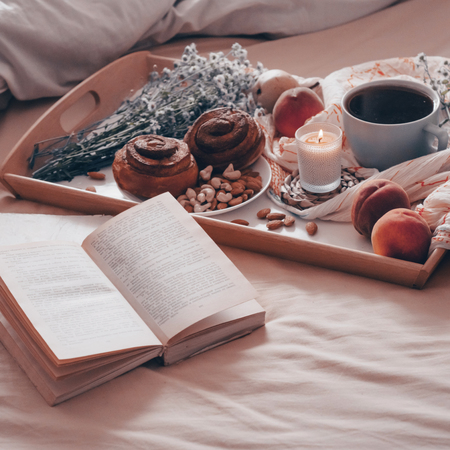 Breakfast in bed, a tray of tea, croissants, fruit, flowers. Morning. Cozy Apartment. Open the book the text is out of focus. Background layout. a day off
