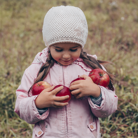 Photo for Happy child holding red apples in his hands. Harvest Funny kid outdoors in autumn park. - Royalty Free Image