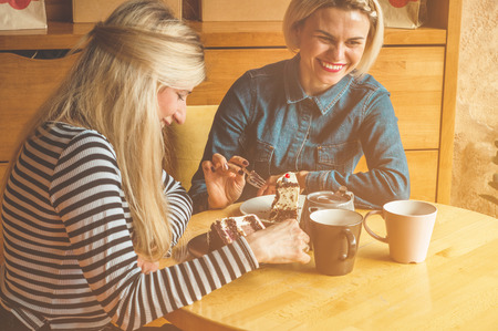 Photo pour Two happy women sitting in a cafe, drink a hot tea, tell each other funny stories, being in a good mood, laughing happily. Best friends - image libre de droit