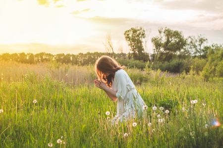 Foto de Girl closed her eyes, praying in a field during beautiful sunset. Hands folded in prayer concept for faith, spirituality and religion. Peace, hope, dreams concept - Imagen libre de derechos
