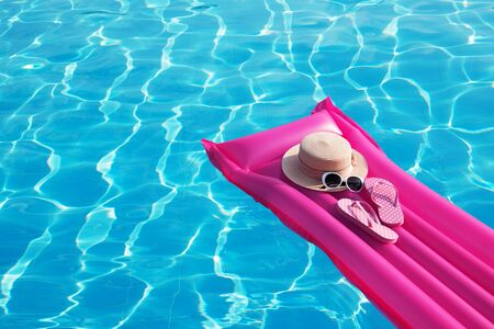 Photo for Beach summer holiday background. Inflatable air mattress, flip flops and hat on swimming pool. - Royalty Free Image