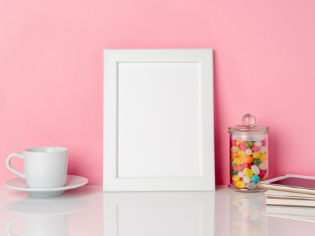 Blank white frame and candys in jar, cup of coffee or tea on a white table against the pink wall with copy space