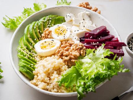 Photo pour Buddha bowl, balanced food, vegetarian menu. Grey marble table, side view. Eggs, avocado, salad lettuce, bulgur, beetroot, tofu - image libre de droit