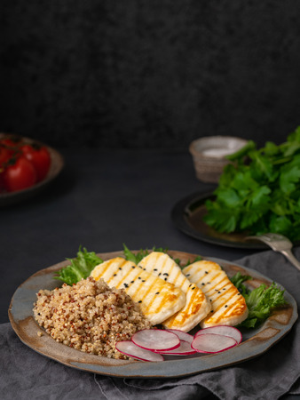 Photo pour Halloumi, grilled cheese with quinoa, salad, radish. Balanced diet on  dark background, copy space - image libre de droit
