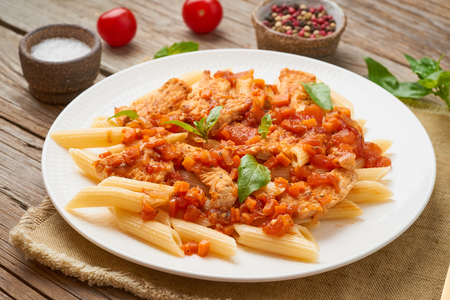 Photo pour Penne pasta, chicken or turkey fillet, tomato sauce with a basil leaves on old rustic wooden background. - image libre de droit