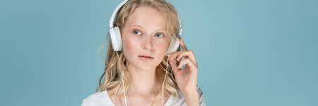 Photo pour Long width banner with portrait of young woman listening music via headphones on color neutral tone Aqua Menthe wall. Pretty serious clever blonde woman with curly hair in white t shirt - image libre de droit