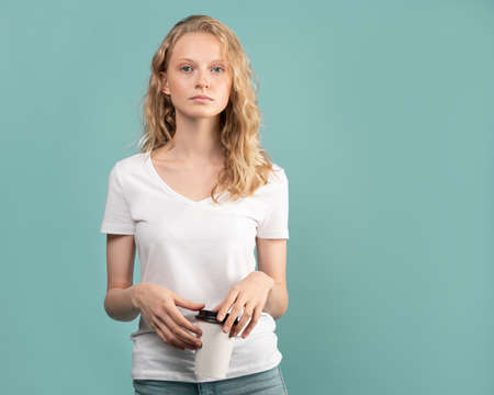 Photo pour Waist-up portrait of beautiful young student girl with cup of coffee on color neutral tone Aqua Menthe wall. Pretty serious clever blonde woman with curly hair in white t shirt - image libre de droit