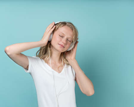 Photo pour Portrait of young woman closed eyes listening music via headphones on color neutral tone Aqua Menthe wall. Pretty serious clever blonde woman with curly hair in white t shirt - image libre de droit