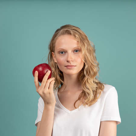 Photo pour Beautiful young serious clever blonde woman without makeup with red apple on color neutral tone Aqua Menthe wall. Pretty female with curly hair in white t shirt - image libre de droit