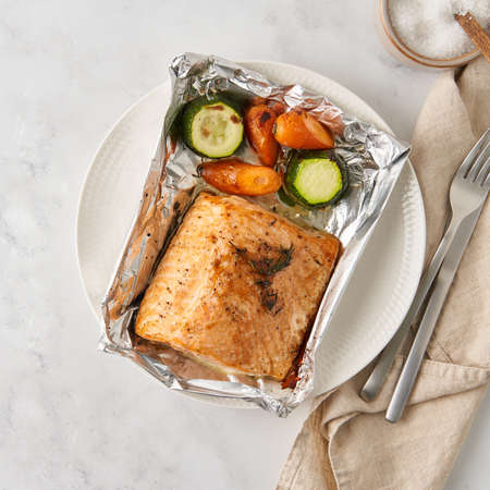 Photo pour Foil pack dinner with fish. Fillet of salmon with vegetables on white plate - zucchini, carrots. Healthy diet food, keto diet, Mediterranean cuisine. Top view - image libre de droit