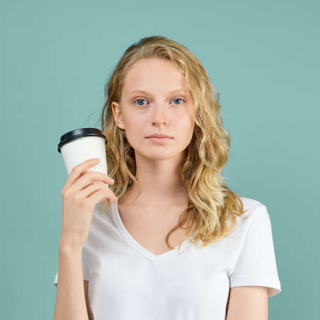 Photo pour Portrait of young student girl with cup of coffee on color bright blue green Aqua Mint wall. Pretty serious clever blonde woman with curly hair in white t shirt - image libre de droit