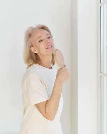 Photo pour Happy carefree mature woman with hairbrush as mic singing her favourite song and having fun at home. Positive eldretly female pretending to be famous singer while standing in front of big window - image libre de droit