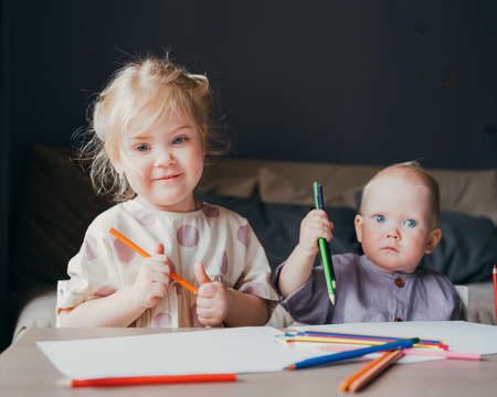Photo for Adorable little girl with golden hair and cute baby boy drawing with colored pencils while sitting at table, older sister playing with small brother while enjoying leisure time together at home - Royalty Free Image