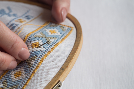 Hands of a woman embroidering a geometric ornament