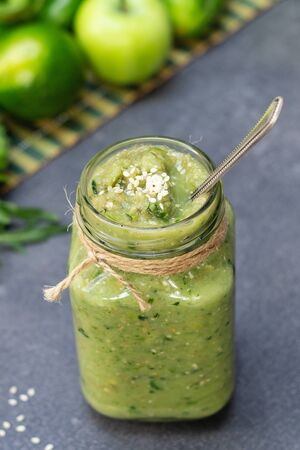 Vegetable green smoothie anh whole ingredients in a glass jar on a dark background