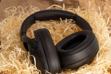 Photo for fashionable stereo headphones in black. top view, lie in paper shavings. - Royalty Free Image