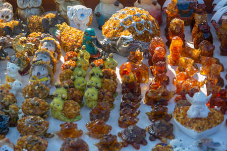 Souvenirs and various figures from amber stones at craft market. Selective focus, close-up.