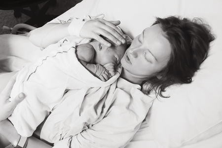 Photo pour Mother holding her newborn baby child after labor in a hospital. Mother giving birth to a baby boy. Black and white photo. - image libre de droit
