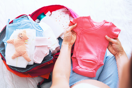 Pregnant woman packing suitcase, bag for maternity hospital at home, getting ready for newborn birth, labor. Pile of baby clothes, necessities and pregnant women at awaiting.