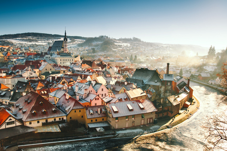 Panoramic view of Cesky Krumlov in winter, Czech Republic. View of the snow-covered red roofs. Travel and Holiday in Europe. Christmas and New Year time. Sunny winter day in european town.