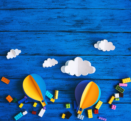 Foto de Creative children's background with copy space for text, top view. Paper crafts, colourful toy bricks on blue wood table. DIY, study languages, kids creativity class, adventure or travel themes - Imagen libre de derechos