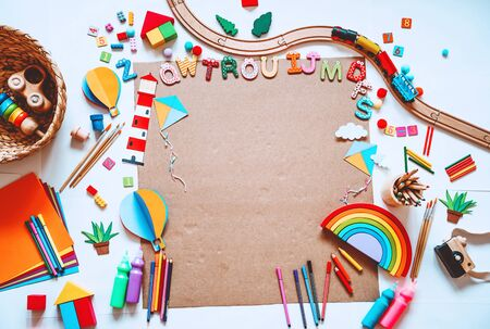 Foto de Background for preschool or kindergarten or art classes. Kids educational toys and school supplies for draw and make DIY crafts. Flat lay top view. Art child frame with empty paper, mock up for text - Imagen libre de derechos