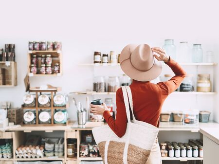 Photo for Minimalist vegan style girl with wicker bag and reusable glass coffee cup on background of interior of zero waste shop. Woman doing shopping without plastic packaging in plastic free grocery store. - Royalty Free Image