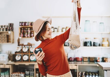 Minimalist vegan style young woman with cotton reusable net mesh bag and reusable glass coffee cup on background of goods of zero waste shop. Shopping without plastic packaging in plastic free store.