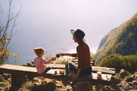 Photo for Beautiful happy family outdoors. Mother and daughter on a picnic in mountains. Mom and child girl holding enameled tourists mugs of hot tea. Adventure travel with kids, camping and hiking in nature. - Royalty Free Image