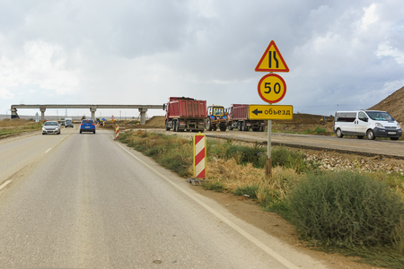 Photo pour Tavrida highway, Crimea, Russia-September 07, 2018: road signs Detour, road narrowing and speed limits on the section of construction roads of the new highway - image libre de droit