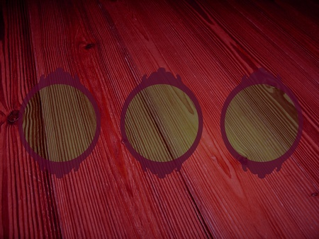 Old pinkish dark red wood background with three circular empty frames for pictures