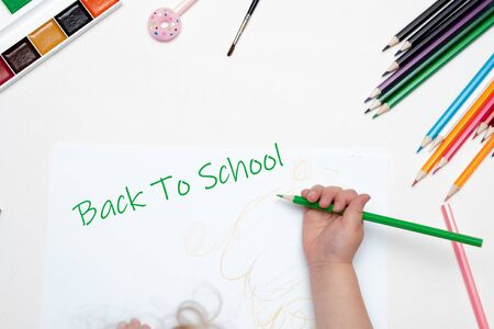 Photo for child hand holds a green pencil draws writes on a white piece of paper white background top view place copy back to school lettering paint pencils brush pink pen with donut - Royalty Free Image