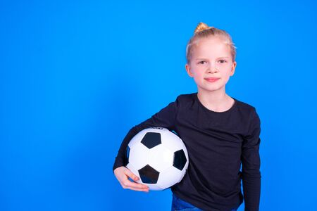 Photo for Soccer fans. Cute blonde girl in black shirt holding soccer ball in hands over blue studio background. Copyspace. Football game - Royalty Free Image