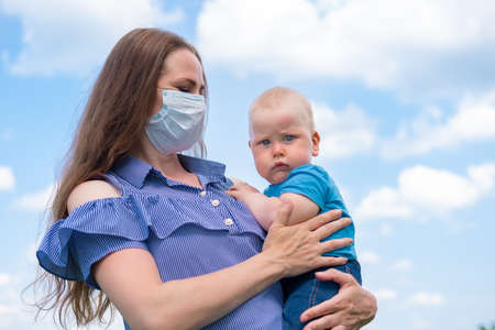Photo for Serios baby on mother hand. Mom in protective medical mask holds her little sonover blue sky at summer. End of coronavirus. - Royalty Free Image
