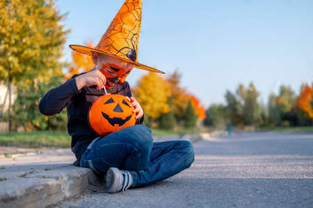 Photo pour Halloween kids. boy with pumpkin face mask in witch costume hat eating candy from buckets sitting on street. - image libre de droit