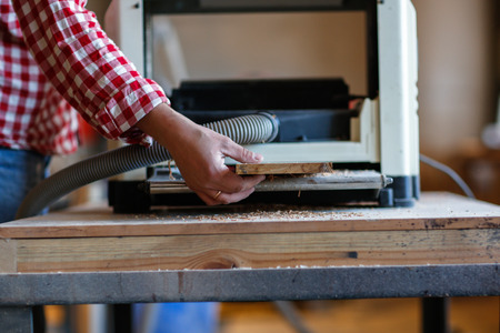 Carpenter working with a wooden board on edging planers, woodworking shop, workshop, tools, close-up